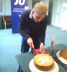 Lars Petersen schneidet im Ratssaal einen JU-Kuchen an